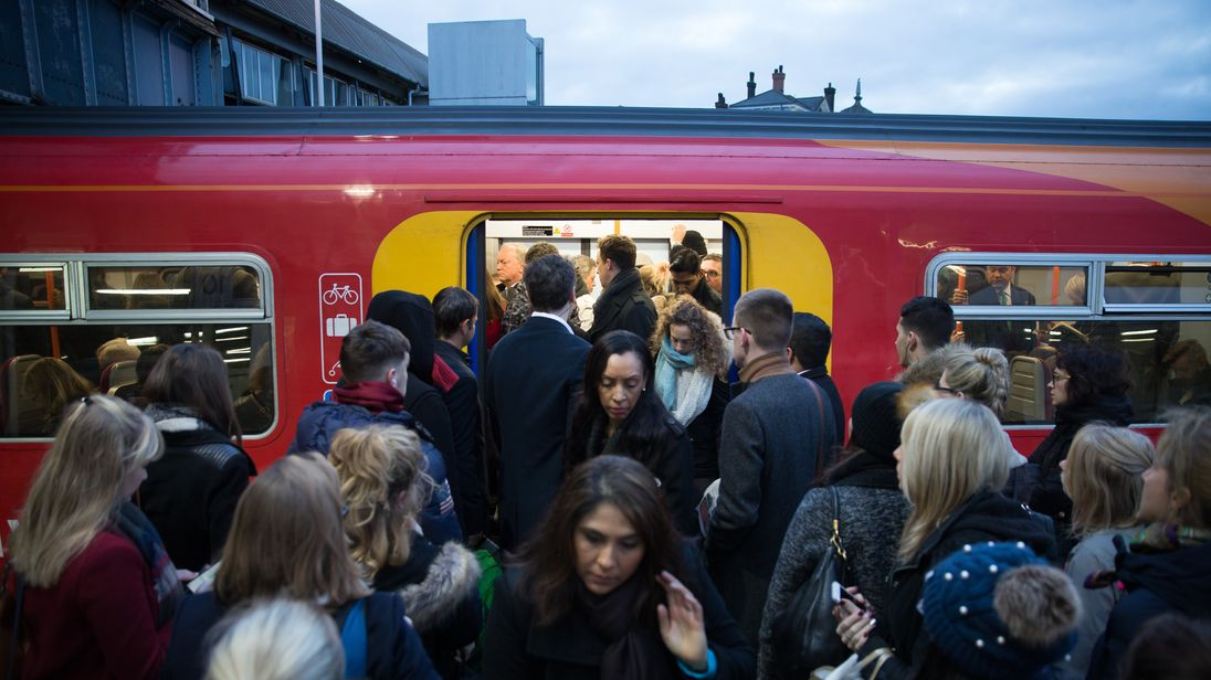 Commuters attempt to board a full Southwest Train carriage