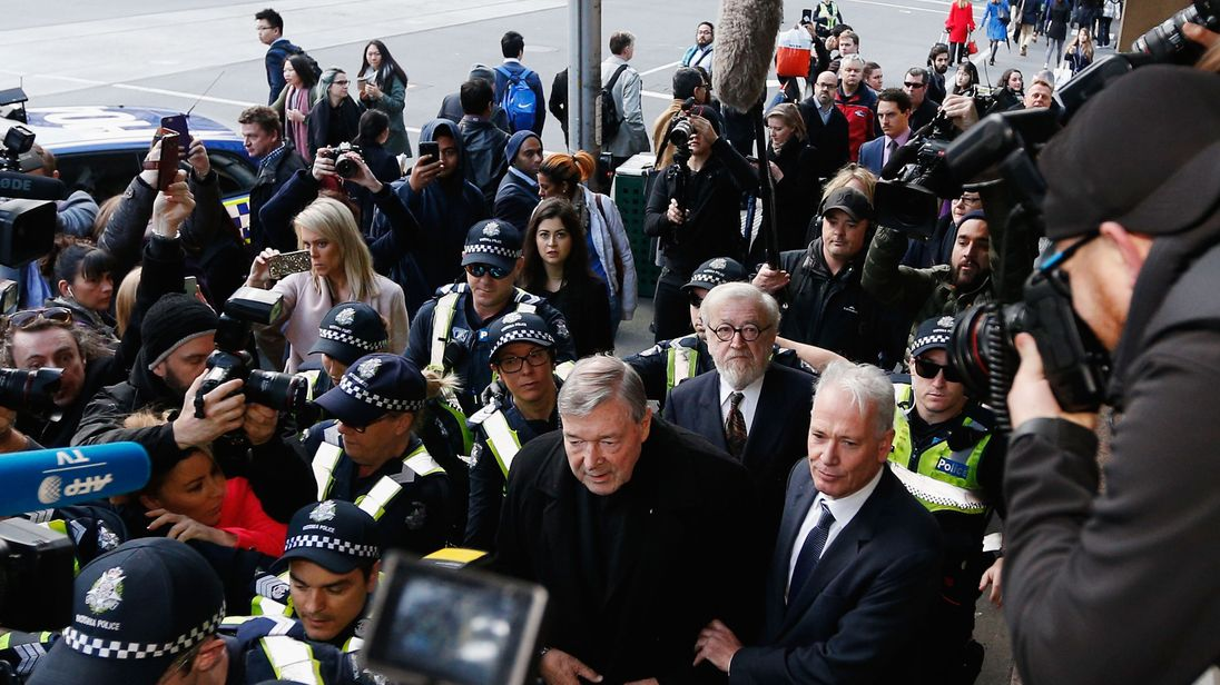 Cardinal George Pell walks with a heavy Police guard to the Melbourne Magistrates' Court on July 26, 2017 in Melbourne, Australia