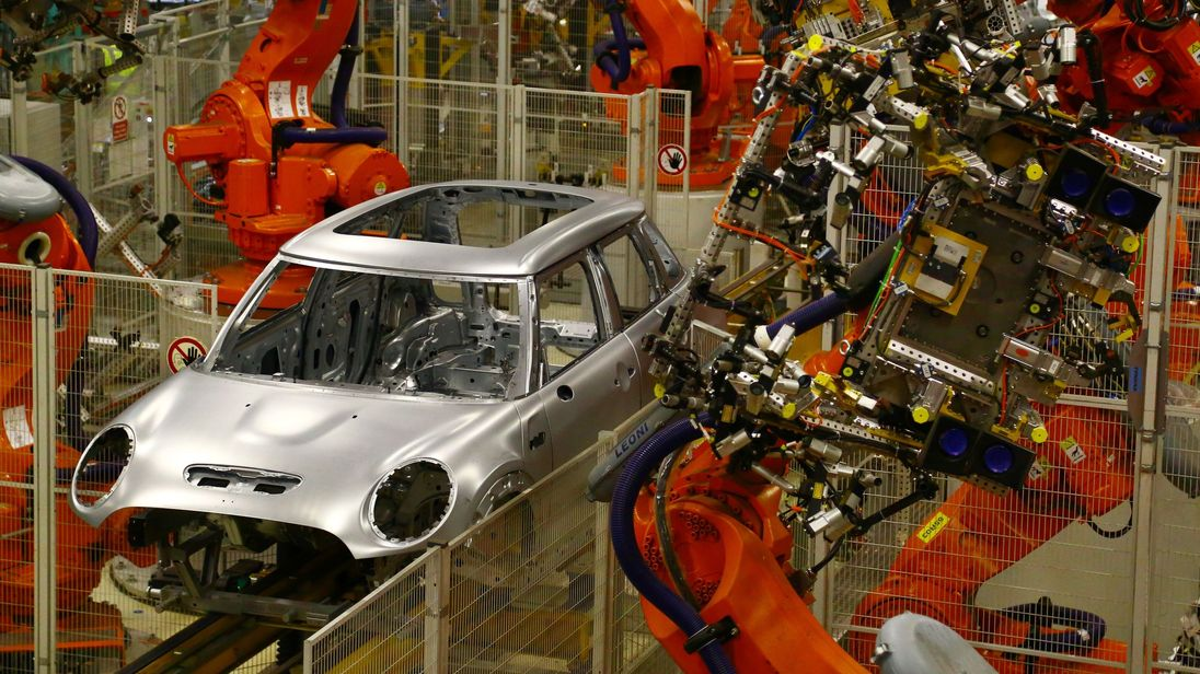 Minis in the 'Body in white' stage of manufacture pass along a robotic assembly line at the BMW Mini car production plant in Oxford, west of London, on January 17, 2017