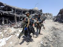 Members of Iraqi Federal police carry suicide belts used by Islamic State militants