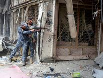 A member of the Iraqi Federal Police opens fire against Islamic State militants