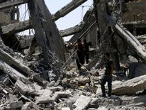 Iraqi security forces walk along destroyed buildings
