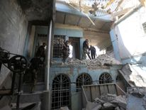 Iraqi Counter Terrorism Service personnel walk in a destroyed building
