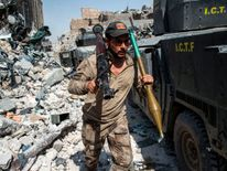 A member of the Iraqi forces walks through the rubble past humvees as he carries a rocket-propelled grenade and launcher