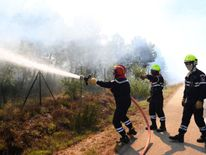 Firefighters try to extinguish a fire burning in Artigues, southeastern France