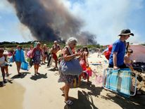Tourists evacuate the beach as smoke fills the sky above a burning hillside in Bormes-les-Mimosas, in the Var department