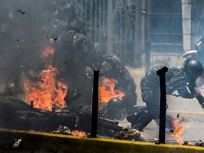 Police officers react after an explosive device exploded as they rode past during a protest against the elections for a Constituent Assembly in Caracas on July 30, 2017