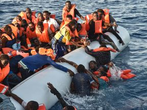 Migrants and refugees panic as they fall in the water during a rescue operation of the Topaz Responder rescue ship run by Maltese NGO Moas and Italian Red Cross, off the Libyan coast in the Mediterranean Sea, on November 3, 2016. / AFP / ANDREAS SOLARO (Photo credit should read ANDREAS SOLARO/AFP/Getty Images)