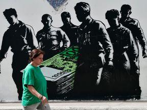 A woman walks past graffiti in the Greek capital Athens