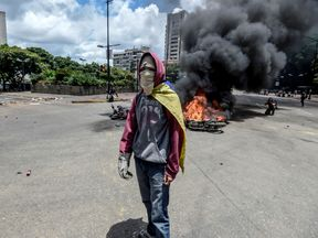 An anti-government activist stands in front of burning police bikes, following the explosion of an explosive device during a protest against the elections for a Constituent Assembly in Caracas on July 30, 2017