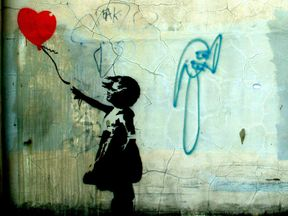 Girl holding a heart balloon. Photograph of Banksy's graffiti street art from 2004