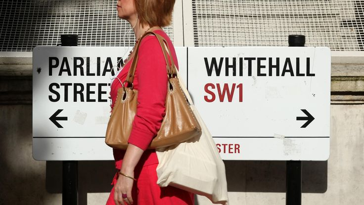 A pedestrian walks past a sign in Whitehall
