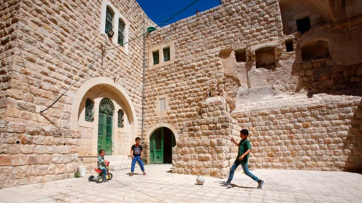 Palestinian children play with a ball outside their house