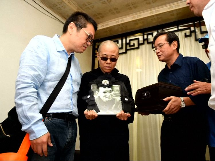 Liu Xiaobo's wife Liu Xia holds a photo of her late husband