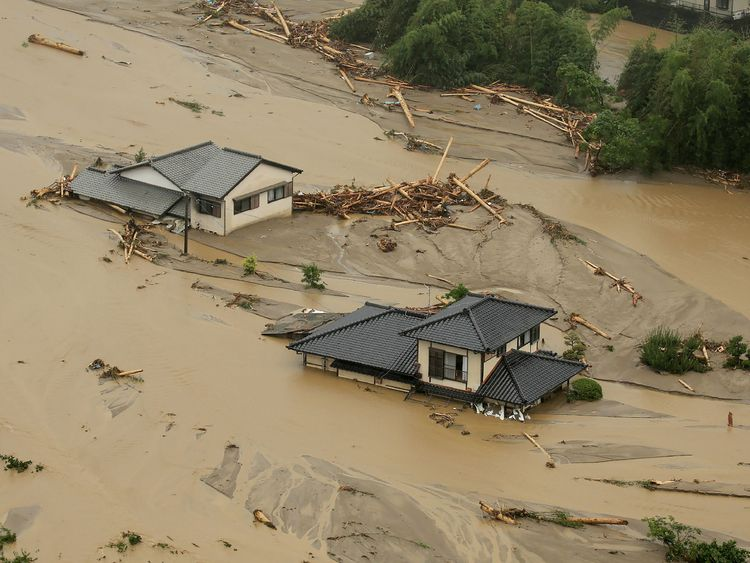 This aerial view shows homes flooded and buried in dirt in the city of Asakura, Fukuoka prefecture