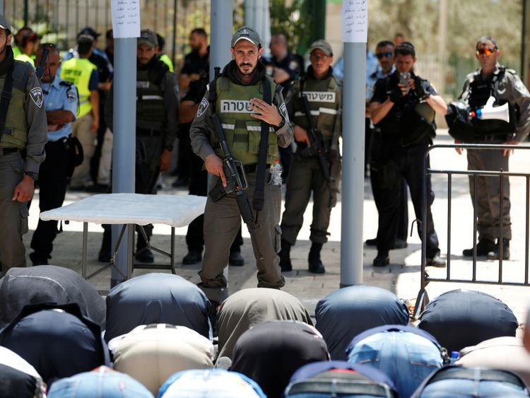 DATE IMPORTED:16 July, 2017Palestinians pray as Israeli police officers look on by newly installed metal detectors at an entrance to the compound known to Muslims as Noble Sanctuary and to Jews as Temple Mount in Jerusalem's Old City July 16, 2017. REUTERS/Ronen Zvulun