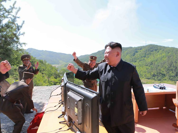 Kim Jong-Un celebrates the launch with military officers