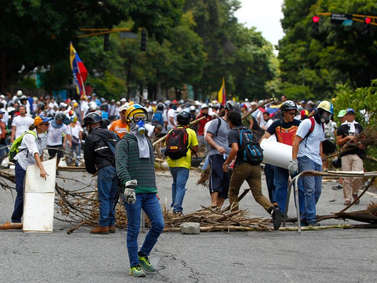 Opposition supporters stand near a barricade in Caracas