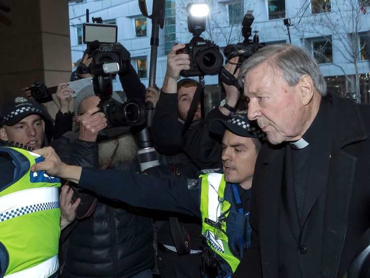 Vatican Treasurer Cardinal George Pell is surrounded by Australian police and members of the media as he arrives at the Melbourne Magistrates Court in Australia, July 26, 2017