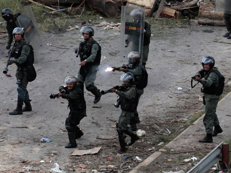 Security forces members point their weapons as one fires at demonstrators