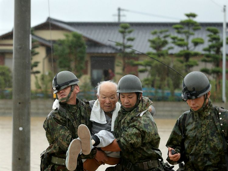 Japanese soldiers help local residents evacuate from flooded area in Asakura, Fukuoka prefecture, on July 6, 2017. At least 15 people are missing after huge floods swept away houses in southern Japan, tearing up roads as roiling waters surged through villages, authorities said, after unprecedented rainfall.JAPAN OUT / AFP PHOTO / JIJI PRESS / STR / Japan OUT (Photo credit should read STR/AFP/Getty Images)