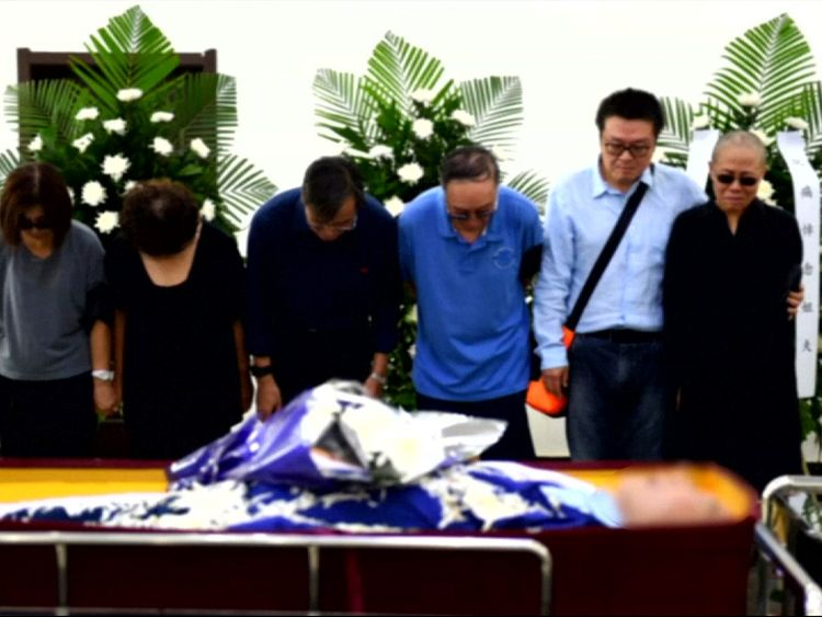 Relatives of Liu Xiaobo stand by the side of his open coffin