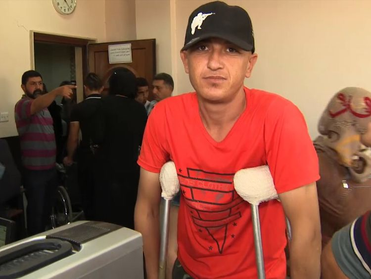 A man on crutches waits in line for treatment