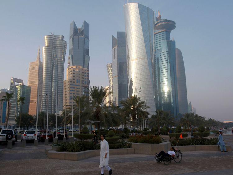 A man walks on the corniche in Doha, Qatar