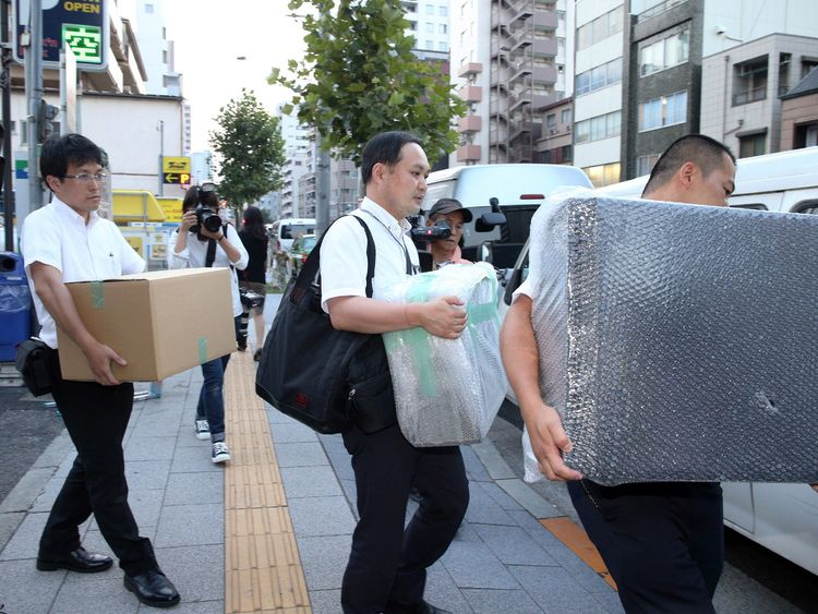 Police officers carry pieces of evidence out of house of Mark Karpeles, the head of defunct Bitcoin exchange MtGox, in Tokyo on August 3, 2015