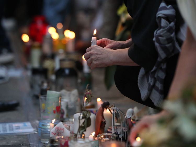 People place candles at the memorial wall on Bramley Road