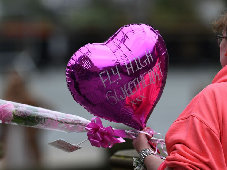 A mourner arrives carrying a rose and a pink balloon