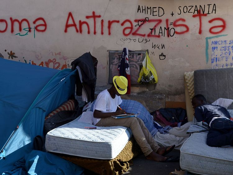 Migrants rest by a graffiti reading 'Rome antiracist' in the street of Via Cupa outside the former Baobab migrant reception centre next to the Tiburtina train station in Rome on August 8, 2016. Set up almost three years ago the Baobab centre was shut down by police in December 2015 in the wake of Paris attacks. But Baobab volunteers quickly set up a camp on the street in front of the old shelter with tents and chemical toilets, serving three meals a day. / AFP / FILIPPO MONTEFORTE