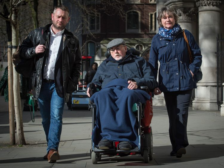 Noel Conway, 67, who suffers from motor neurone disease, arrives at the Royal Courts of Justice in London where he is seeking a judicial review in his fight for the right to have the option of an assisted death, with his wife Carol (right) and stepson Terry McCusker (left).