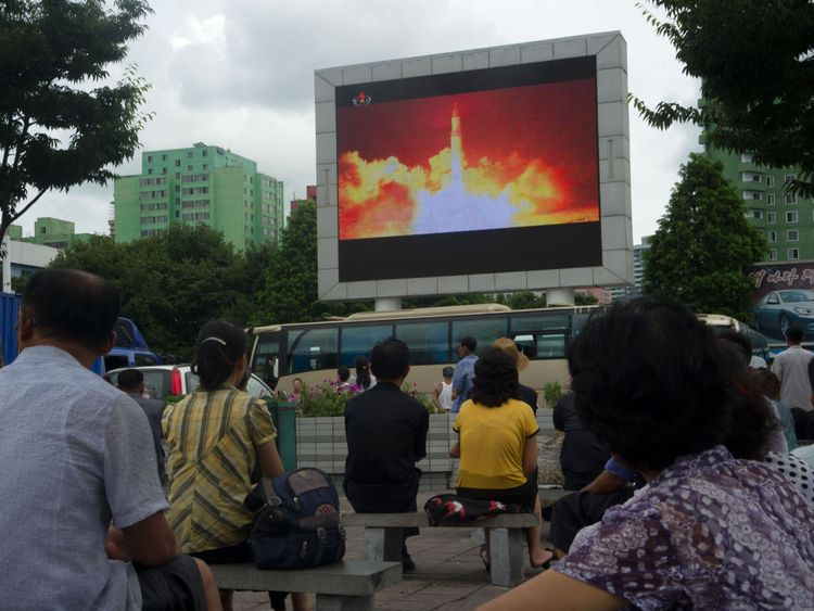 People watch the ICBM missile test is displayed on a screen in a public square in Pyongyang