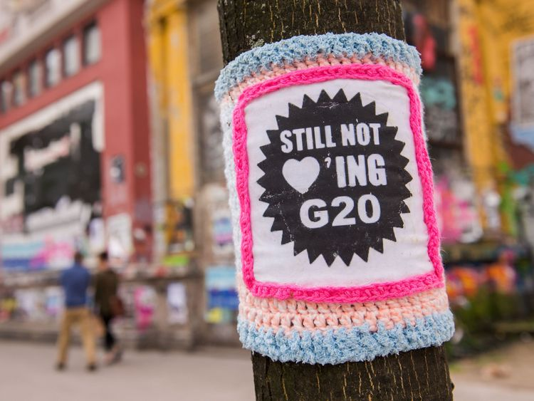 tree is wrapped into a crocheted protest banner reading 'Still not loving G20' on July 5, 2017 in Hamburg, northern Germany, ahead of a two-day G20 summit. The Group of 20 (G20) comprising leaders of the world's major industrialised and emerging economies will meet from July 7 to 8 in the Hanseatic city. Around 15,000 police will be deployed to protect the summit, in addition to 3,800 officers monitoring airport and train security. / AFP PHOTO / dpa / Daniel Bockwoldt / Germany OUT (Photo credi