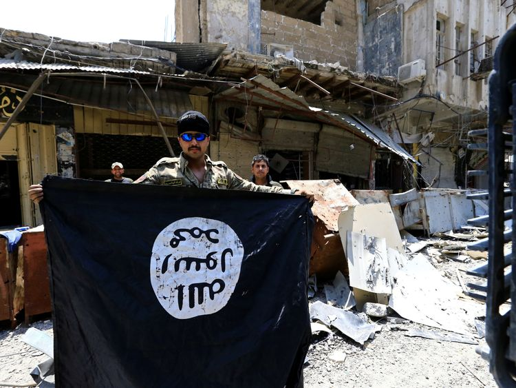 An Iraqi soldier holds an Islamic State flag in Mosul's recaptured Old City