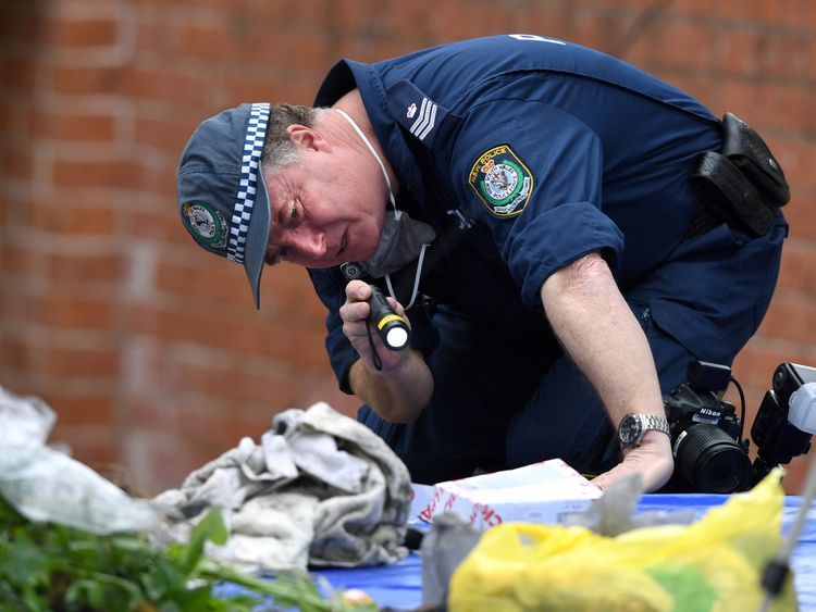 An Australian police officer searches items seized from a property during a raid in the Sydney suburb of Lakemba, Australia, July 31, 2017. AAP/Paul Miller/via REUTERS ATTENTION EDITORS - THIS PICTURE WAS PROVIDED BY A THIRD PARTY. NO RESALES. NO ARCHIVE. AUSTRALIA OUT. NEW ZEALAND OUT.