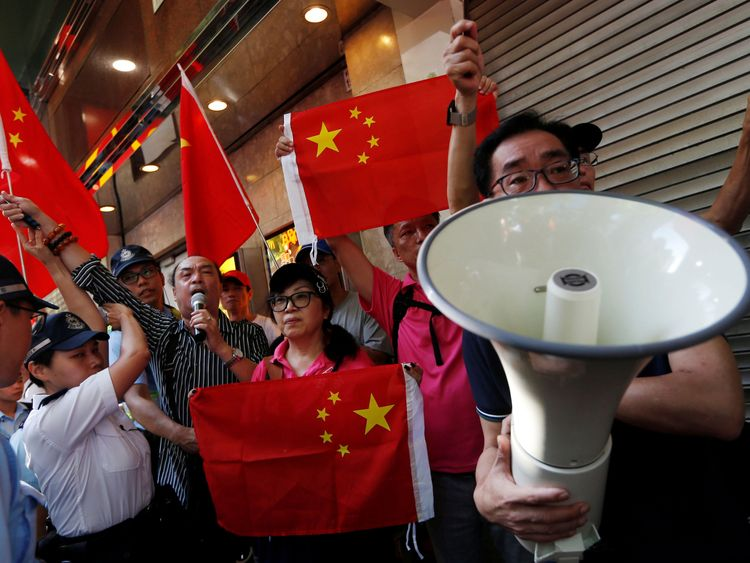 Pro-China supporters hold Chinese flags as they try to stop pro-democracy activists from protesting