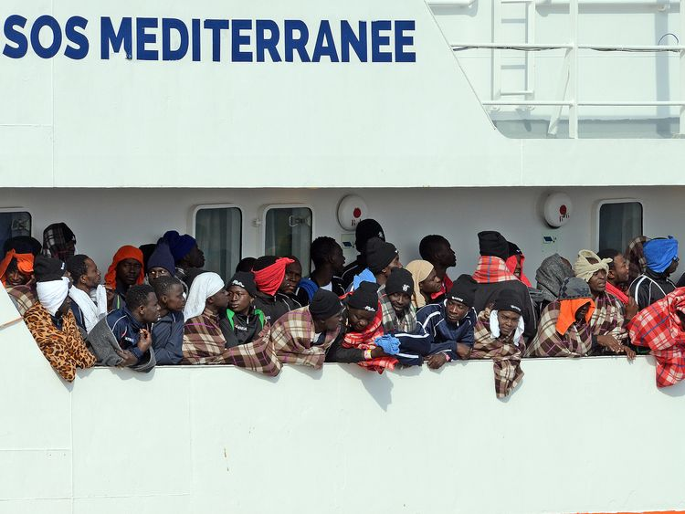 Would be immigrants wait to disembark in the port of Catania, on the island of Sicily on March 21, 2017 from the ship 'Aquarius' following a rescue operation in the Mediterranean sea, where some 946 would be immigrants have been rescued. The Aquarius, a humanitarian ship run by the NGO SOS Mediterranean and Doctors Without Borders (MSF), said it saved 946 people, including 200 unaccompanied minors rescued after being found drifting on nine wooden and rubber boats. / AFP PHOTO / Giovanni ISOLINO