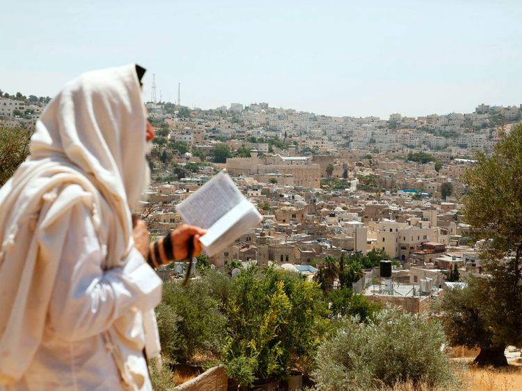 An Israeli settler reads a holy book as he overlooks the Ibrahimi Mosque
