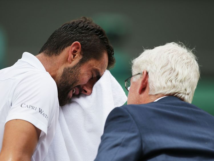 An emotional Maric Cilic is given assistance during the Wimbledon final