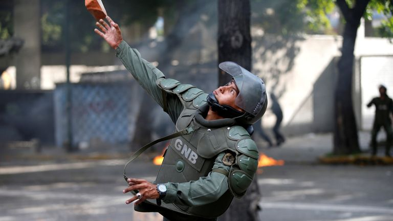 A member of the riot security force throws a piece of brick