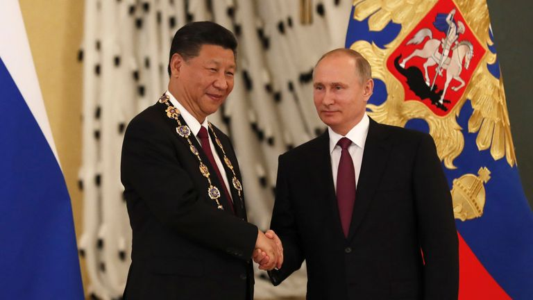 Russian President Vladimir Putin shakes hands with his Chinese counterpart Xi Jinping