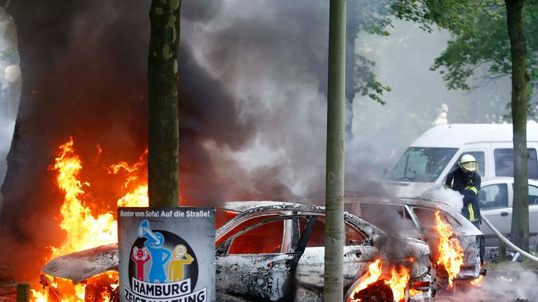 Firefighters work at the scene where a number of cars burnt down during the G20 summit in Hamburg, Germany