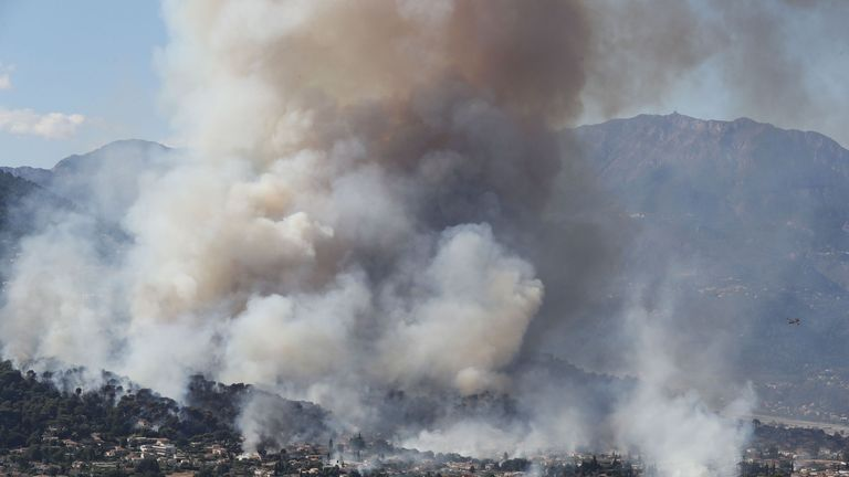 A fire fighting Canadair aircraft flies to drop water over a fire near Carros, southeastern France