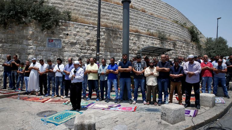 Palestinian Muslim worshippers pray outside Lions' Gate, a main entrance to the Al Aqsa mosque compound