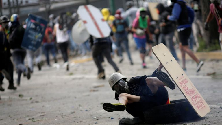 A demonstrator falls down while running away