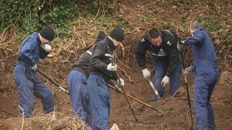 Police officers dig in the grounds of the former children's home Haut De La Garenne