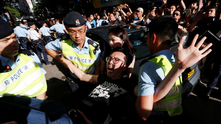 A pro-democracy activist is detained by police as he takes part in a protest