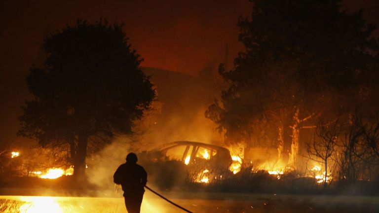 A firefighter runs with a hose as he works to put out a fire in Biguglia, on the French Mediterranean island of Corsica